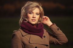 Young blond fashion woman in classic beige coat walking outdoor Royalty Free Stock Image