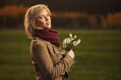 Happy young blond fashion woman wearing classic beige coat walking outdoor stock photos