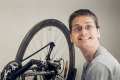 Happy young blond man with short haircut in a gray t-shirt with. Glasses looking at camera and sitting near spinning wheel of dirty broken bicycle stock photography