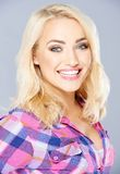 Happy young blond woman with a beaming smile Stock Images