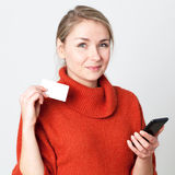 Happy young blond woman consuming on cell phone with credit card Royalty Free Stock Photography