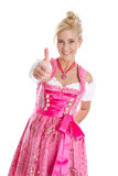 Happy young blond woman in dirndl dress in bavarian folkart. Royalty Free Stock Photos