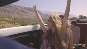 Woman in cabriolet. Happy young blond woman enjoying a white convertible car ride. Pretty blonde girl riding in cabriolet with raised hands on a warm summer day stock video