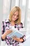 Happy young blond woman holding books Stock Photo