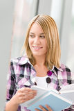 Happy young blond woman holding books Stock Photos