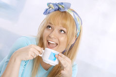 Happy young blond woman smiling and drinkin coffee Stock Images