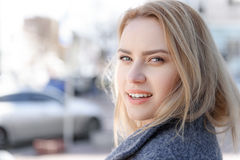 Happy young blond woman walking in town Royalty Free Stock Image