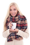 Happy young blond woman in warm clothes with cup of coffee or te Royalty Free Stock Images