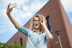 Happy young blonde caucasian woman taking a selfie portrait with mobile phone at the modern brick wall building background Stock Photos
