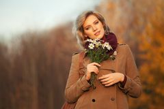 Happy young blond fashion woman wearing classic beige coat walking outdoor stock image