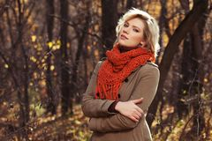 Young blond fashion woman in beige classic coat walking outdoor royalty free stock photos