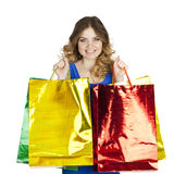 Happy young blonde girl with colorful shopping bags in blue sexy Stock Images