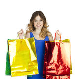 Happy young blonde girl with colorful shopping bags in blue sexy Royalty Free Stock Photo
