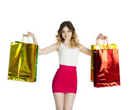 Happy young blonde girl with colorful shopping bags in red skirt Royalty Free Stock Photos