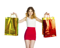 Happy young blonde girl with colorful shopping bags in red skirt Stock Photo