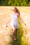 Happy Young Blonde Girl In White Dress With Straw Hat Running Th Stock Photo