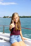 Happy young blonde girl shows ok sign on ship at sea Stock Photos