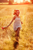 Happy young blonde girl in white dress with straw hat running Royalty Free Stock Images