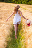 Happy young blonde girl in white dress with straw hat running th Stock Images