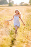 Happy young blonde girl in white dress with straw hat running th Royalty Free Stock Image
