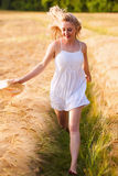 Happy young blonde girl in white dress with straw hat running th Stock Image