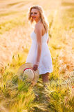 Happy young blonde girl in white dress with straw hat running th Stock Photos