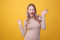 Happy young blonde lady with bright makeup lips. Image of happy young blonde lady with bright makeup lips posing over yellow background. Looking at camera Royalty Free Stock Images