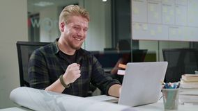 A Young Blonde Man Working on the Laptop Indoors. A happy young blonde men working on the laptop indoors. Medium shot. Soft focus Stock Photography