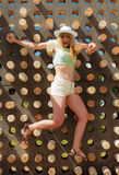 Happy young blonde woman climbing up in adventure park Stock Photo
