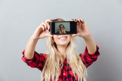 Happy young blonde woman make selfie by phone. Stock Photography