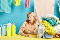 Happy young blonde woman pointing at dishwashing liquid bottle royalty free stock photo