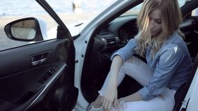 Happy young blonde woman sitting in a white car. stock video footage