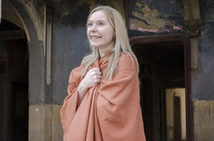 Happy young blonde woman smiling. In old castle, in orange poncho and looking Royalty Free Stock Images