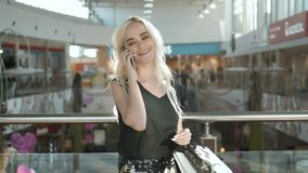 Happy young blonde woman using cell phone at a shopping center, beautiful student girl shopping in mall