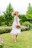 Happy young blonde woman walking barefoot on the green grass Royalty Free Stock Image