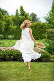 Happy young blonde woman walking barefoot on the green grass Stock Photos