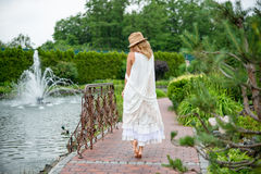 Happy young blonde woman walking barefoot in the park Stock Photo
