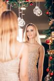 Happy young blonde woman wears a Golden dress and looks in the mirror in the new year stock images