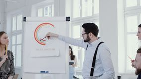 Happy young boss businessman explaining sales diagram on flipchart at modern office seminar event slow motion RED EPIC. Professional business colleagues stock footage