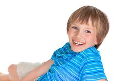 Happy young boy. Portrait of happy young boy lying on white studio background with copy space Royalty Free Stock Photos