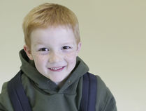 Happy Young Boy With Backpack. Closeup portrait of happy young boy with backpack over colored background Stock Images