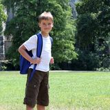 Happy young boy with backpack. Closeup shot of a happy young boy carrying a backpack standing in a park of school - school concept royalty free stock photography