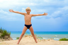 Happy young boy in the beach. Happy young boy with his arms wide open in the sandy beach Royalty Free Stock Image