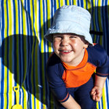 Happy young boy at beach on stripy beach towel. Royalty Free Stock Photos