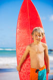 Happy young boy at the beach with surfboard Stock Images
