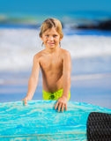 Happy young boy at the beach with surfboard Stock Photo