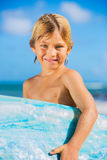 Happy young boy at the beach with surfboard Royalty Free Stock Photography