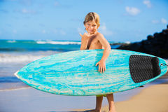 Happy young boy at the beach with surfboard Royalty Free Stock Photo