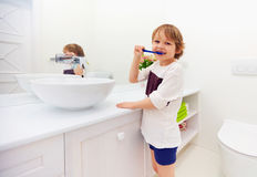 Happy young boy brushing teeth in bathroom stock images