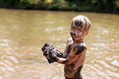 Muddy Little Boy Child Laughing as He Swims and Plays Outside in River royalty free stock photos